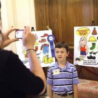 Photo - Duke second-grader Kellen Cansler poses for a photo with his mother, Melissa, on Tuesday at the state Capitol. Kellen won second place among second-graders in the Oklahoma Energy Resources Board's coloring contest.