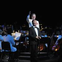 Photo - Surrounded by members of the Oklahoma City Philharmonic, conductor Jack Everly heralds George Takei, narrator of the