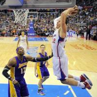 Photo - Los Angeles Clippers forward Blake Griffin, right, goes up for a dunk as Los Angeles Lakers center Dwight Howard, left, and guard Steve Nash, center, look on during the second half of their NBA basketball game, Friday, Jan. 4, 2013, in Los Angeles. The Clippers won 107-102.  (AP Photo/Mark J. Terrill)
