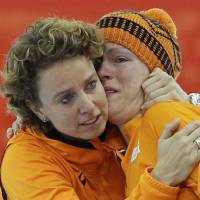 Photo - An emotional Jorien ter Mors of the Netherlands, right, is hugged by team member Renate Groenwold after she won gold for the women's 1,500-meter speedskating race at the Adler Arena Skating Center during the 2014 Winter Olympics in Sochi, Russia, Sunday, Feb. 16, 2014. (AP Photo/Patrick Semansky)