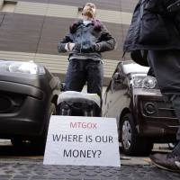 Photo -  Bitcoin trader Kolin Burges stands in protest outside an office building housing Mt. Gox in Tokyo. AP Photo   Shizuo Kambayashi - AP