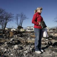 Photo -   Cathy O'Hanlon poses in front of the charred remains of her home in the Breezy Point section of the Queens borough of New York, Wednesday, Nov. 14, 2012. A fire destroyed more than 50 homes in the oceanfront community during Superstorm Sandy. O'Hanlon and her husband plan to rebuild the house. (AP Photo/Mark Lennihan)