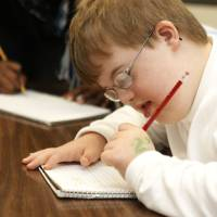 Photo - Special needs student Seth Puffinbarger works on penmanship in instructor Angie Absher's class at Johnson Elementary School. Photo by Paul Hellstern, The Oklahoman  PAUL HELLSTERN