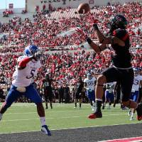 Photo -   Texas Tech's Darrin Moore makes a touchdown catch in front of Kansas' Greg Brown during their NCAA college football game in Lubbock, Texas, Saturday, Nov. 10, 2012. (AP Photo/Lubbock Avalanche-Journal, Zach Long) LOCAL TV OUT
