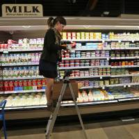 Photo - Grocery and dairy assistant Reyna DeLoge stocks dairy products that only use milk from pasture-raised cows, at Vitamin Cottage Natural Grocers, in Denver, Friday May 23, 2014. The Colorado-based grocery store chain recently announced that it will carry only dairy products from farms where cows graze on pasture, taking the position that grazing improves the health of cows and consumers. (AP Photo/Brennan Linsley)