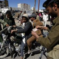 Photo - Yemeni soldiers check a motorbike driver at a checkpoint in Sanaa, Yemen, Saturday,  Jan. 5, 2013. Yemeni police have said that more than 40 security and army personnel were shot dead in drive-by attacks involving motorbikes throughout Yemen in 2012. (AP Photo/Hani Mohammed)