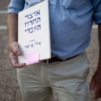 Photo -   In this Wednesday, June 13, 2012 photo, Israeli author Eli Tziper holds a copy of his book