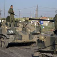 Photo - Russian solders with their several military vehicle gather at the rail road crossing about 30 kilometers (19 miles) from Ukrainian border at  Rostov-on-Don region, Russia, early Friday, Aug. 15, 2014. (AP Photo/Pavel Golovkin)