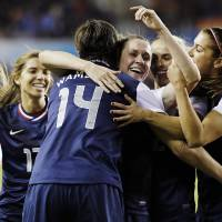 Photo - United States' Abby Wambach (14) celebrates with teammates after scoring a goal during the first half of an exhibition soccer match against China, Wednesday, Dec. 12, 2012, in Houston. (AP Photo/David J. Phillip)