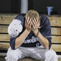 Photo - North Carolina's Chris McCue sits in the dugout after losing 4-1 to UCLA in an NCAA College World Series baseball game in Omaha, Neb., Friday, June 21, 2013. UCLA won 4-1. (AP Photo/Eric Francis)