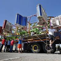 Photo -  Workers with Great Plains Amusements from Rush Springs set up rides for the annual Lions Club Carnival in downtown Norman. PHOTO BY STEVE SISNEY, THE OKLAHOMAN   STEVE SISNEY -