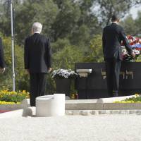 Photo - U.S. President Barack Obama, right, with Israeli President Shimon Perez, center, and Israeli Prime Minister Benjamin Netanyahu stand behind, lays a wreath at the grave of Theodor Herzl during his visit to Mt. Herzl in Jerusalem, Israel, Friday, March 22, 2013. (AP Photo/Pablo Martinez Monsivais)