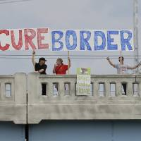 Photo - FILE - This July 18, 2014, file photo shows demonstrators with signs on an overpass in Indianapolis, to protest against people who immigrate illegally. Even as they grapple with an immigration crisis at the border, White House officials are making plans to act before November's mid-term elections to grant work permits to potentially millions of immigrants in this country illegally, allowing them to stay in the United States without threat of deportation, according to advocates and lawmakers in touch with the administration. (AP Photo/Darron Cummings, File)