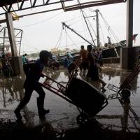 Photo - Migrant workers unload frozen fish from a boat at a fish market in Samut Sakhon Province, west of Bangkok, Friday, June 20, 2014. The United States has blacklisted Thailand and Malaysia for failing to meet its minimum standards in fighting human trafficking, a move that could strain relations with two important U.S. partners in Asia. Thailand had mounted a determined campaign to prevent a downgrade that could exact a reputational cost on its lucrative seafood and shrimp industries for which America is a key market. (AP Photo/Sakchai Lalit)