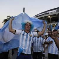 Photo - Argentina fans wave their nation's flag and cheer as their team's bus arrives carrying the players to Maracana Stadium for their World Cup soccer match with Bosnia in Rio de Janeiro, Brazil, Sunday, June 15, 2014. (AP Photo/Matt Dunham)