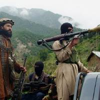 Photo - FILE - In this file photo taken on Aug. 5, 2012, Pakistani Taliban patrol in their stronghold of Shawal in Pakistani tribal region of South Waziristan. The Pakistani army said it has launched a