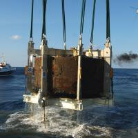 Photo - FILE This Monday Aug. 5, 2002 file photo shows the turret of the Civil War ironclad USS Monitor is lifted out of the ocean off the coast of Hatteras NC.  A century and a half after the USS Monitor sank, the interment of remains of two unknown sailors found in the Civil War ironclad's turret is bringing together nearly 100 people from Maine to California who have a distant familial tie to the 16 Union sailors who died when the ship went down. (AP Photo/Steve Helber)