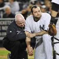 Photo -   A trainer, left, helps New York Yankees relief pitcher Joba Chamberlain who was hit by a broken bat when Baltimore Orioles' Matt Wieters hit a single during the twelfth inning of Game 4 of the American League division baseball series on Thursday, Oct. 11, 2012, in New York. (AP Photo/Bill Kostroun)