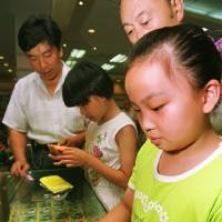 Photo - FILE - In this July 13, 1997 file photo, nine-year-old Zhu Ying tries out a Tamagotchi electronic pet at a Beijing department store. Bandai America Inc. and Sync Beatz Entertainment are hoping to revive the electronic pet craze of the 1990s with a new mobile app launching Thursday, Feb. 14, 2013, for Android devices. The app duplicates the egg-shaped plastic toy that became a must-own sensation after it was first released in 1996 in Japan. (AP Photo/Greg Baker, File)