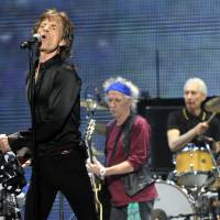 Photo - Mick Jagger, left, Keith Richards, center, and Charlie Watts of the Rolling Stones perform on the kick-off of the band's
