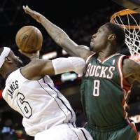 Photo - Milwaukee Bucks center Larry Sanders (8) attempts to block a shot by Miami Heat forward LeBron James (6) during the first half of Game 2 in their first-round NBA basketball playoff series, Tuesday, April 23, 2013 in Miami. The Heat defeated the Bucks 98-86. (AP Photo/Wilfredo Lee)