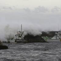 Photo - Big waves go over breakwater near anchored fishing boats in Fujisawa, near Tokyo, Monday, Sept. 16, 2013. Powerful typhoon Man-yi was bearing down on Japan and went past Tokyo on Monday, leaving one dead and dumping torrential rains, damaging homes and flooding parts of the country's popular tourist destination of Kyoto, where hundreds of thousands of people were ordered to evacuate to shelters. (AP Photo/Shizuo Kambayashi)