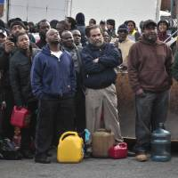 Photo -   A crowd gather at a service station with portable containers, waiting for gas pumps to open, Saturday, Nov. 3, 2012 in the Brooklyn borough of New York. Mayor Michael Bloomberg said that resolving gas shortages could take days. Police presence was increased at gas lines after arrests at gas stations over line jumping. (AP Photo/Bebeto Matthews)