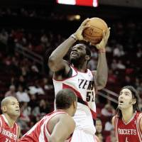 Photo - Portland Trailblazers' Greg Oden, top, drives to the basket past Houston Rockets' Luis Scola, right, and Shane Battier (31) during a NBA basketball game on Saturday, Oct. 31, 2009 in Houston. (AP Photo/Bob Levey) ORG XMIT: TXBL102
