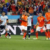 Photo - Argentina's Lionel Messi, left, shoots a free-kick past the Dutch defense during the World Cup semifinal soccer match between the Netherlands and Argentina at the Itaquerao Stadium in Sao Paulo, Brazil, Wednesday, July 9, 2014. (AP Photo/Frank Augstein)