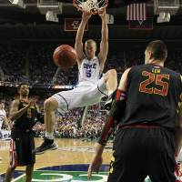 Photo - Duke's Mason Plumlee (5) dunks as Maryland's Alex Len (25) and Nick Faust (5) look on during the second half of an NCAA college basketball game at the Atlantic Coast Conference tournament in Greensboro, N.C., Friday, March 15, 2013. Maryland won 83-74. (AP Photo/Gerry Broome)