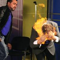 Photo - In this picture released by American magician Wayne Houchin, Dominican TV presenter Franklin Barazarte, left, watches as Houchin's head burns while taping