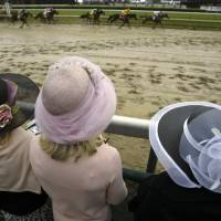 Photo - Racing fans wearing colorful hats watch the eighth race at Churchill Downs, Friday, April 30, 2004, in Louisville, Ky. The 130th kentucky Derby is slated for Saturday, may 1 at the track. (AP Photo/Amy Sancetta)  AMY SANCETTA - AP