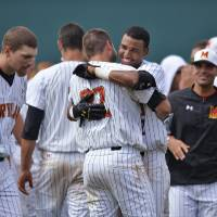 Photo - Maryland's Jose Cuas, center, hugs teammate Kyle Convissar (22) after Maryland defeated Old Dominion 4-3 during an NCAA college baseball tournament regional game in Columbia, S.C.,  Friday, May 30, 2014. (AP Photo/Richard Shiro)