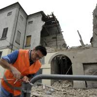Photo -   A volunteer ropes off the area surrounding a collapsed building in Finale Emilia, northern Italy after a quake hit northern Italy early Sunday, May 20, 2012. One of the strongest earthquakes to shake northern Italy rattled the region around Bologna early Sunday, a magnitude-6.0 temblor that killed at least four people, toppled buildings and sent residents running into the streets, emergency services and news reports said. (AP Photo/Marco Vasini)