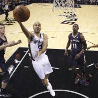 Photo - San Antonio Spurs' Tony Parker (9), of France, scores against the New Orleans Pelicans during the first half of an NBA basketball game, Monday, Nov. 25, 2013, in San Antonio. (AP Photo/Eric Gay)