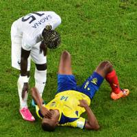 Photo - Ecuador's Osvaldo Minda, right, is attended by France's Bacary Sagna during the group E World Cup soccer match between Ecuador and France at the Maracana Stadium in Rio de Janeiro, Brazil, Wednesday, June 25, 2014. (AP Photo/Francois Xavier Marit, pool)
