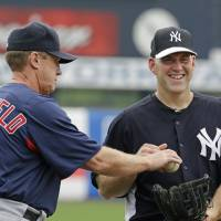 Photo - Boston Red Sox third base coach Brian Butterfield, left, puts a ball into the glove of New York Yankees third baseman Kevin Youkilis, a former Red Sox infielder, before a spring training baseball game in Tampa, Fla., Wednesday, March 20, 2013.  (AP Photo/Kathy Willens)