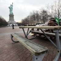 Photo - A warped picnic bench sits with other debris on Liberty Island, in New York,  Friday, Nov. 30, 2012. Tourists in New York will miss out for a while on one of the hallmarks of a visit to New York _ seeing the Statue of Liberty up close. Though the statue itself survived Superstorm Sandy intact, damage to buildings and Liberty Island's power and heating systems means the island will remain closed for now, and authorities don't have an estimate on when it will reopen. (AP Photo/Richard Drew)