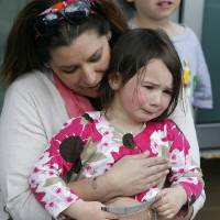 Photo - Stacey Tracy, of Cranston, R.I., comforts her daughter Emily Tracy, 4, after she found out the 3:00 p.m. show of the Ringling Bros. and Barnum & Bailey Circus had been canceled, Sunday, May 4, 2014, in Providence, R.I.  A platform collapsed during an aerial hair-hanging stunt at the 11 a.m. performance Sunday, sending eight acrobats plummeting to the ground. At least nine performers were seriously injured in the fall, including a dancer below, while an unknown number of others suffered minor injuries. (AP Photo/Stew Milne)