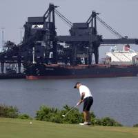 Photo - ADVANCE FOR MONDAY, JULY 28, 2014, AT 12:01 A.M. AND THEREAFTER -  In this May 22, 2014, photo, a ship is docked at Norfolk Southern's Lamberts Point coal terminal as a man plays golf in Norfolk, Va. As the Obama administration weans the U.S. off dirty fuels blamed for global warming, energy companies have been sending more of America's unwanted energy leftovers to other parts of the world, where they could create even more pollution. (AP Photo/Patrick Semansky)