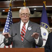 Photo - House Minority Whip Steny Hoyer of Md., joined by Rep. Maxine Waters, D-Calif., left, and Rep. Kerry Bentivolio, R-Mich., criticizes the efforts of Republicans to muscle legislation through the House authorizing an election-year lawsuit against President Barack Obama that accuses him of exceeding his powers in enforcing his health care law, Wednesday, July 30, 2014, during a news conference on Capitol Hill in Washington. Democrats have branded the effort a political charade aimed at stirring up Republican voters for the fall congressional elections. They say it's also an effort by top Republicans to mollify conservatives who want Obama to be impeached — something House Speaker John Boehner of Ohio, said Tuesday he has no plans to do.  (AP Photo/J. Scott Applewhite)