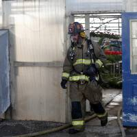 Photo - A firefighters exists a greenhouse following a fire at TLC Florists and Greenhouses, located at 105 W. Memorial Rd., near Memorial and Santa Fe in Oklahoma City, Friday, Feb. 21, 2014. Photo by Sarah Phipps, The Oklahoman