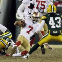 Photo - San Francisco 49ers quarterback Colin Kaepernick (7) slides as he runs against Green Bay Packers defense during the second half of an NFL wild-card playoff football game, Sunday, Jan. 5, 2014, in Green Bay, Wis. (AP Photo/Mike Roemer)