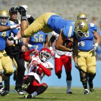 Photo -   UCLA tight end Joseph Fauria, top, leaps over Utah defensive back Eric Rowe (18) for 12 yards and a first down during the first half of their NCAA college football game, Saturday, Oct. 13, 2012, in Pasadena, Calif. (AP Photo/Alex Gallardo)