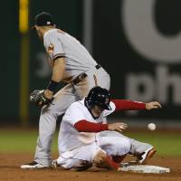 Photo - Boston Red Sox's Brock Holt, bottom, is safe at second base on a missed catch error by Baltimore Orioles' Ryan Flaherty in the seventh inning of a baseball game in Boston, Sunday, April 20, 2014. (AP Photo/Michael Dwyer)