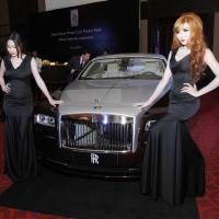 Photo -  Models pose beside a Rolls-Royce Wraith during the inauguration of its official dealership Monday in Phnom Penh, Cambodia.  AP Photo   Heng Sinith -  AP