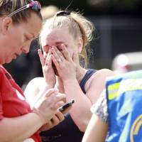 Photo - A person wipes away tears as they await to hear about the safety of students after a shooting at Reynolds High School Tuesday, June 10, 2014, in Troutdale, Ore. A gunman killed a student at the high school east of Portland Tuesday and the shooter is also dead, police said. (AP Photo/The Oregonian, Faith Cathcart)  MAGS OUT; TV OUT; LOCAL TV OUT; LOCAL INTERNET OUT; THE MERCURY OUT; WILLAMETTE WEEK OUT; PAMPLIN MEDIA GROUP OUT