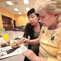 Photo - Education intern Jessica Lie works with dementia patient Peggy Morrison on an art project at the Oklahoma City Museum of art. Photo by David McDaniel, The Oklahoman  David McDaniel - The Oklahoman