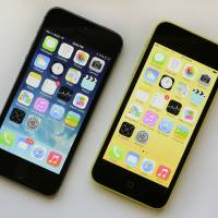Photo - The iPhone 5S, left, and iPhone 5c are displayed Tuesday, Sept. 17, 2013, in New York.  The 5S offers a fingerprint sensor, a better camera and a faster processor, while the iPhone 5C is largely last year's iPhone 5 with a plastic back and a choice of five colors. (AP Photo/Mark Lennihan)