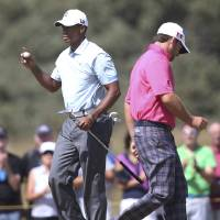 Photo - Tiger Woods of the United States, left, holds up his ball after putting on the 14th green as Graeme McDowell of Northern Ireland prepares to putt during the second round of the British Open Golf Championship at Muirfield, Scotland, Friday July 19, 2013. (AP Photo/Scott Heppell)